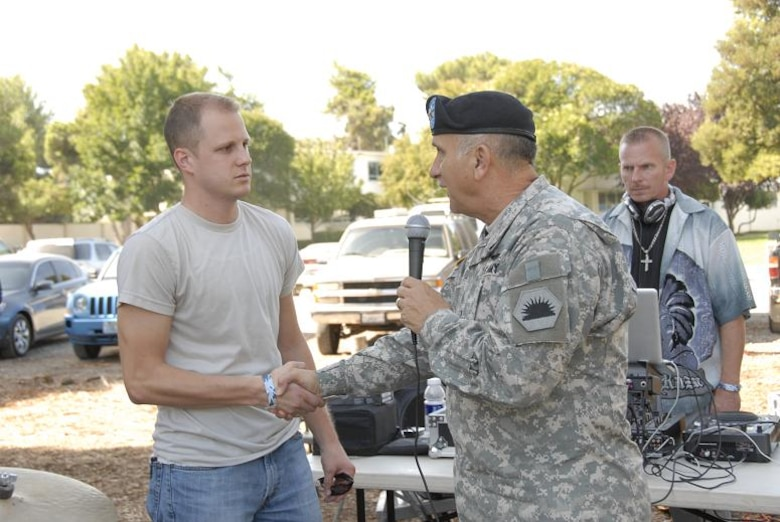 Maj. Gen. William H. Wade, the California Adjutant General, congratulates Senior Airman James Parmentier, a guidance and control systems avionics technician with the 129th Aircraft Maintenance Squadron, at the 129th Rescue Wing's annual Family Day Picnic hosted Oct. 3 at Moffett Federal Airfield, Calif. for winning the John L. Levitow award for his accomplishments at Airman Leadership School. (Air National Guard photo by Tech. Sgt. Ray Aquino)