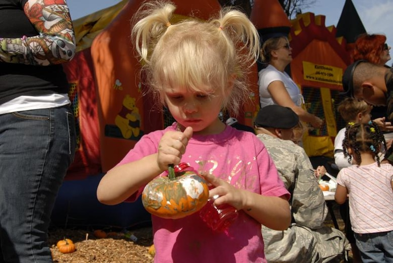 Molly Mae Theodoroff, daughter of Master Sgt. Timothy Theodoroff, a satellite technician with the 129th Communications Flight, takes a time out from the bounce houses to admire her arts and crafts pumpkin at the 129th Rescue Wing's annual Family Day Picnic hosted Oct. 3 at Moffett Federal Airfield, Calif. (Air National Guard photo by Tech. Sgt. Ray Aquino)