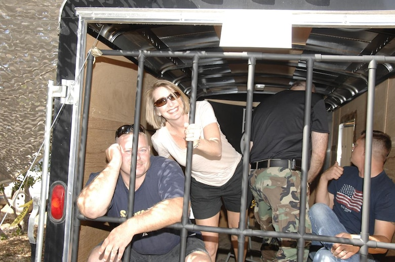 Command Chief Master Sgt. Kristina Keck and Master Sgt. Kenneth Warwick, the NCOIC telephone technician from the 129th Communications Flight, wait with fellow prisoners to make bail in the makeshift jail at Moffett Federal Airfield, Calif. controlled by the 129th Security Forces Squadron Oct. 3 during the 129th Rescue Wing's annual Family Day Picnic. (Air National Guard photo by Master Sgt. Dan Kacir)
