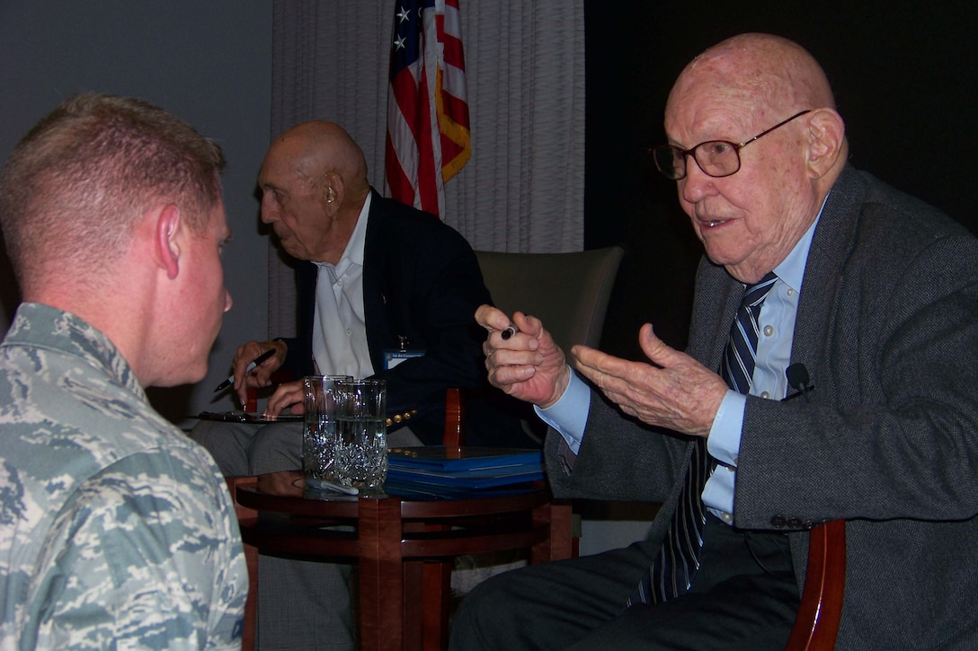 Retired Maj. Gen. John Elison, right, speaks with an airman during the Air Commando Heritage Symposium at the Air Force Special Operations Training Center auditorium at Hurlburt Field Oct. 9. (U.S. Air Force photo by Airman 1st Class Joe McFadden.)