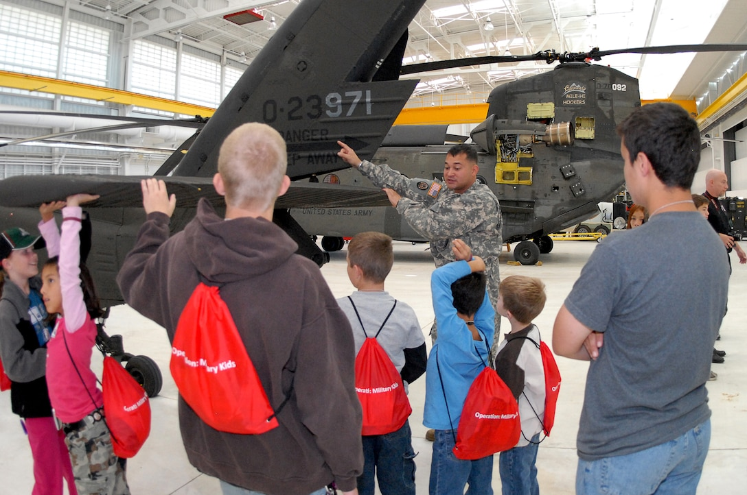 Army 1st Lt. Bryant Ronald, Helicopter Pilot, explains how the military uses helicopters during the Buckley Air Force Base Youth Mock Deployment, Oct 3.  This event was held to help children understand what their parents see and experience during a deployment. (U.S. Air Force photo by Tech. Sgt. J. LaVoie)