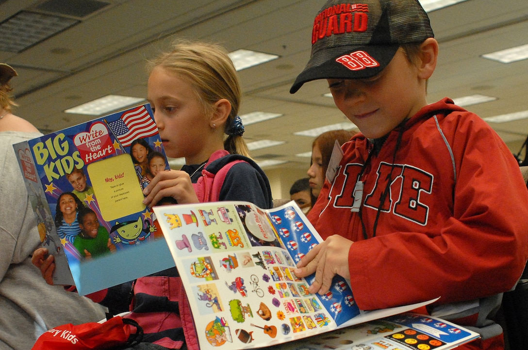 """Michaela and Austin Gromer  check out the stickers and goodies they received in their """"deployment"""" bags during the Buckley Air Force Base youth mock deployment, Oct 3.  Though the deployment was Buckley's first """"Year of the Air Force Family"""" event, it was truly joint as children from all four services, including active, guard and reserve, attended.  (U.S. Air Force photo by Tech. Sgt. J. LaVoie)"""