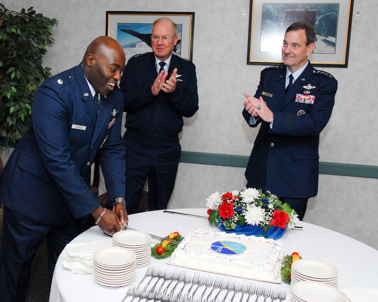 (From right) Gen. Stephen Lorenz, Air Education and Training Command commander, and Gen. Craig McKinley, chief of National Guard Bureau, applaud Lt. Col. Ronald Daniels, the new Detachment 12, Air National Guard Readiness Center commander as he cuts a cake during the activation ceremony Oct. 2. (U.S. Air Force photo/Bud Hancock)