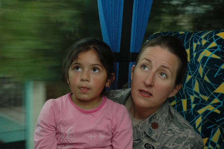 SANTIAGO, Chile -- Maj. Jana Nyerges, a member of Air Forces Southern participating in subject matter exchange with the Chilean Air Force in Santiago, Chile, and her new-found friend, a child from the Centro Comunitario Angels, or 'Angels Community Center' watch cartoons on the bus after spending the day at the Museo Interactivo Mirador.  A group of Airmen sponsored children from the school to visit the museum after landing in country only a few hours.  (Courtesy photo)