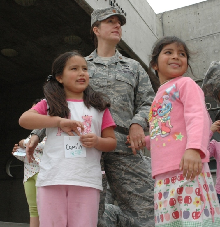SANTIAGO, Chile -- Maj. Jana Nyerges, a member of Air Forces Southern participating in a subject matter exchange with the Chilean Air Force in Santiago, Chile, waits with children from the Centro Comunitario Angels, or 'Angels Community Center,' outside the Museo Interactivo Mirador prior to sponsoring the children's admission to the science exhibits.  Airmen decided to use their first day in Chile to sponsor a group of at-risk children during a visit to the museum. (Courtesy photo)