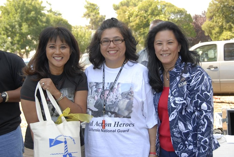 Leslie Wade (right), wife of Maj. Gen. William H. Wade, the California Adjutant General, and Carolann Wunderlin (left), the 129th Rescue Wing Family Readiness Program coordinator, present a gift to Elaine Vindiola, 129th Mission Support Group Spouse of the Year award winner Oct. 4 at the annual Family Day Picnic at Moffett Federal Airfield, Calif. (Air National Guard photo by Tech. Sgt. Ray Aquino)