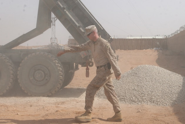 A Marine with Transportation Support Company, Combat Logistics Battalion 46, signals to the dump truck operator that he is clear to move after dumping his load of stones at Combat Outpost 160K, Iraq, where Engineer Company Marines are to conduct repairs and upgrades to the base, Oct. 16, 2009.  One of the tasks they are performing is correcting a major drainage problem the base is having, which is causing a pool of waste water to form just outside the base perimeter. (U.S. Marine Corps photograph by Lance Cpl. Melissa A. Latty)