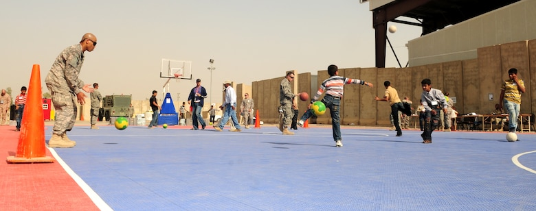 JOINT BASE BALAD, Iraq -- Servicemembers play sports with local children at the H-6 recreation center during Iraqi Kids Day here Oct. 10, 2009. (U.S. Air Force photo/Staff Sgt. Heather M. Norris)