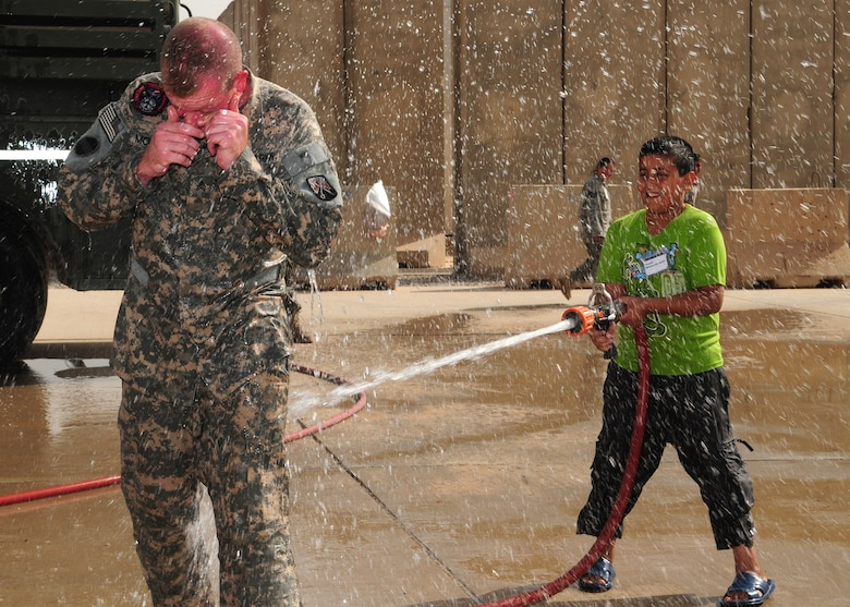 JOINT BASE BALAD, Iraq -- An Iraqi boy soaks Army Sgt. Joshua McGinnis, 23rd Ordnance Company firefighter, during the Iraqi Kids Day here Oct. 10, 2009. Sergeant McGinnis is deployed here from Grafenwoehr, Germany, and is a native of Springfield, Mo. (U.S. Air Force photo/Staff Sgt. Heather M. Norris)