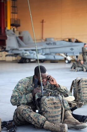 Sgt. Detren Tate, radio operator with Company A, 1st Battalion, 2nd Marine Regiment, programs his radio equipment on the flight line at the Marine Corps Air Station in Yuma, Ariz., prior to a long-distance night helicopter raid exercise Oct. 16, 2009. The company took off from Yuma in six CH-53s and two MV-22 Ospreys to seize an airfield and rescue an enemy defector and his family, as well as retrieve valuable communication equipment, at Fort Huachuca near Tucson, Ariz. The training was in preparation for the battalion's upcoming deployment to Afghanistan in the spring of 2010.
