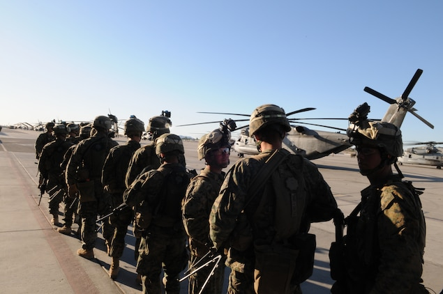 Marines from Company A, 1st Battalion, 2nd Marine Regiment, line up on the flight line at the Marine Corps Air Station in Yuma, Ariz., before boarding a CH-53 helicopter for a long-distance night helicopter raid exercise Oct. 16, 2009. The company took off from Yuma in six CH-53s and two MV-22 Ospreys to seize an airfield and rescue an enemy defector and his family, as well as retrieve valuable communication equipment, at Fort Huachuca near Tucson, Ariz. The training was in preparation for the battalion's upcoming deployment to Afghanistan in the spring of 2010.