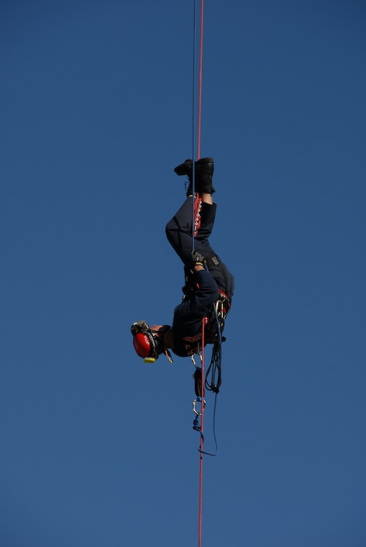 Senior Master Sgt. David Maupin, 231st Civil Engineer Flight, dangles upside down during a rappel demonstration done for servicemembers at Lambert International Airport Oct. 18 in honor of Fire Safety Month to show the members some of the local firefighters training. (Photo by Master Sgt. Mary-Dale Amison)