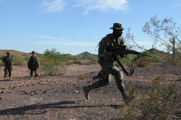 A Marine from Headquarters and Service Company, 1st Battalion, 2nd Marine Regiment, rushes forward as his fellow Marines look on during infantry tactics training at Graze Range at the U.S. Army Yuma Proving Ground in Arizona, Oct. 18, 2009. Comprised of Marines with noninfantry specialties, the Camp Lejeune, N.C.-based company is preparing to operate as an infantry company during their upcoming deployment to Afghanistan in the spring of 2010.