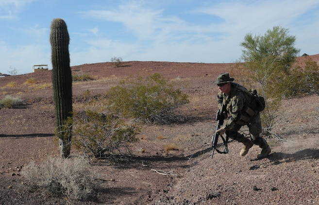 Lance Cpl. Ben Norville, an armory custodian with Headquarters and Service Company, 1st Battalion, 2nd Marine Regiment, rushes forward during infantry tactics training at Graze Range at the U.S. Army Yuma Proving Ground in Arizona, Oct. 18, 2009. Comprised of Marines with noninfantry specialties, the Camp Lejeune, N.C.-based company is preparing to operate as an infantry company during their upcoming deployment to Afghanistan in the spring of 2010.