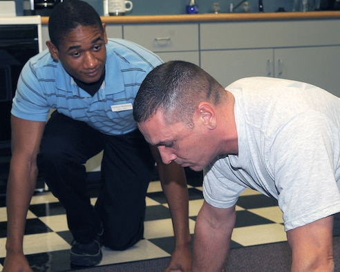 WHITEMAN AIR FORCE BASE, Mo. -- Nathan Berkley, a student intern at the Whiteman Health and Wellness Center, observes pushups performed by Senior Master Sgt. Samuel Simmons, Superintendant, 509th Operations Support Squadron.  The duo demonstrated proper push-up form at a Physical Training Leader refresher course, Monday.