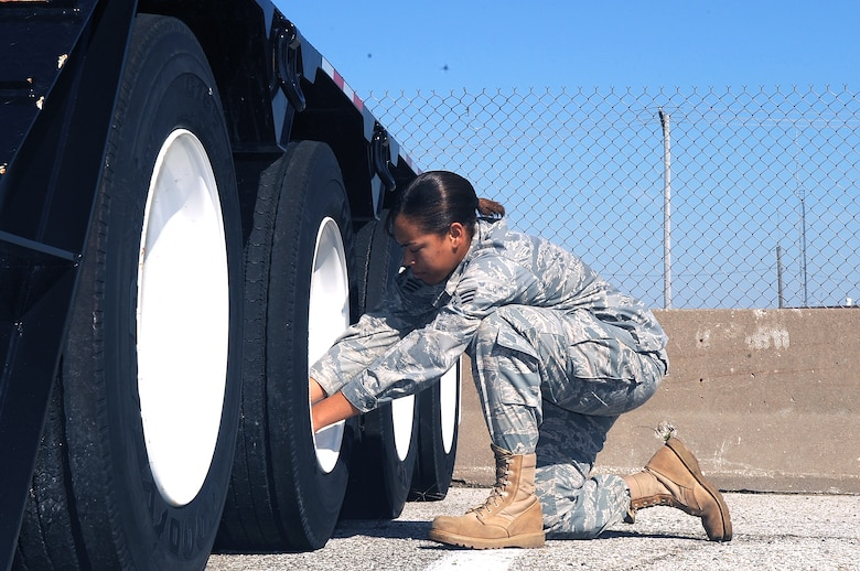 "WHITEMAN AIR FORCE BASE, Mo. -- Senior Airman Kristin Campbell, 509th Logistics Readiness Squadron vehicle operator, verifies each tire on her ""low boy"" trailer is inflated to the correct level.  Operators must inspect their equipment before each driving assignment.