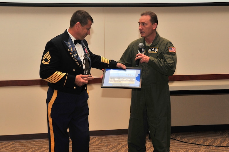 Col. Clint Crosier, 460th Space Wing commander recognizes Retired Sgt. 1st Class Dana Bowman with a memento at the National Disability Employee Awareness event, Oct. 16. Sergeant Bowman was a member of the Army's elite parachute team, the Golden Knights, and became the first double amputee to re-enlist into the U. S. Army. (U.S. Air Force photo by Airman 1st Class Manisha Vasquez)
