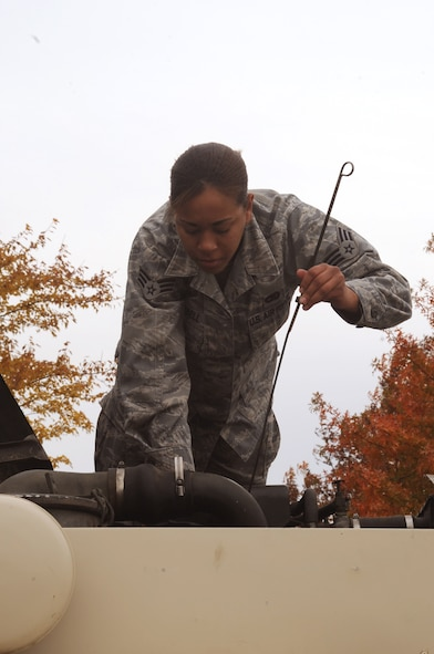 """WHITEMAN AIR FORCE BASE, Mo. -- Senior Airman Kristin Campbell, 509th Logistics Readiness Squadron Vehicle Operator, withdraws the oil level indicator from a """"deuce-and-a-half"""" truck before an assignment.  Operators must inspect thier equipment before each driving assignment."""