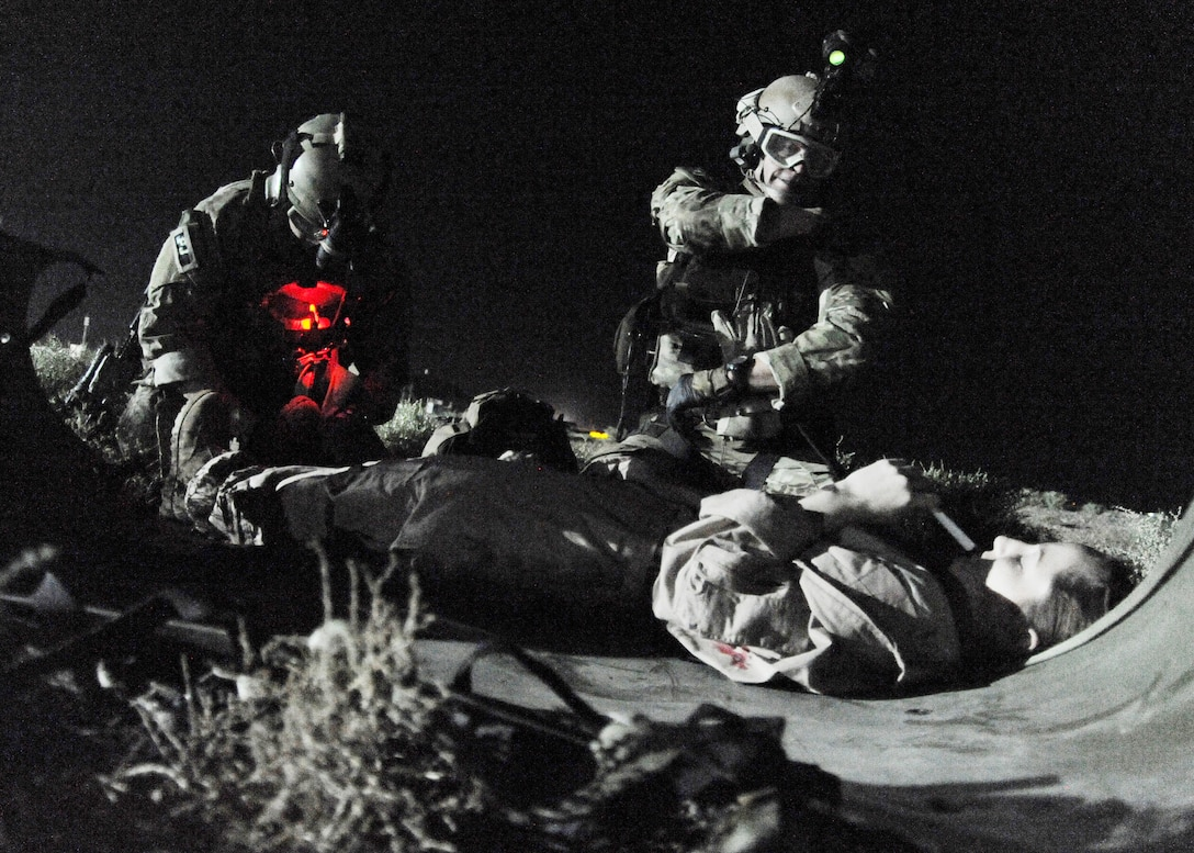 "Staff Sgt. Joshua Kruse and Senior Airman Nate Simonson administer aid to a ""patient"" during a night training exercise Oct. 20, 2009, at Joint Base Balad, Iraq. The exercise simulated a nighttime extraction scenario emphasizing the rappelling portion of the pararescue mission. The Airmen are assigned to the 64th Expeditionary Rescue Squadron. (U.S. Air Force photo/Senior Airman Christopher Hubenthal)"