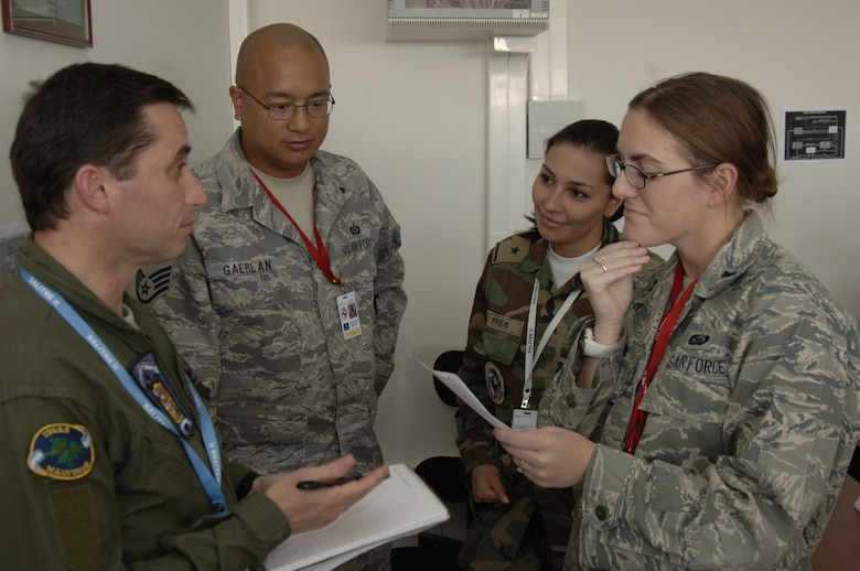 ANTOFAGASTA, Chile -- (From left to right) Maj. Gianotti Javier, Argentinian Air Force, Staff Sgt. Drew Gaerlan, 612th Air Operations Center, 2nd Lt. Stephanie Fres, Fuerza Aérea de Chile or FACH, and Capt. Nicole Golden, 612th AOC, discuss intelligence planning Oct. 20 at Cerro Moreno Air Base during SALITRE, a multinational exercise sponsored by Chile to promote interoperability. Chile, Brazil, France, Argentina and the United States are participating in the exercise. (U.S. Air Force photo by Tech. Sgt. Eric Petosky)
