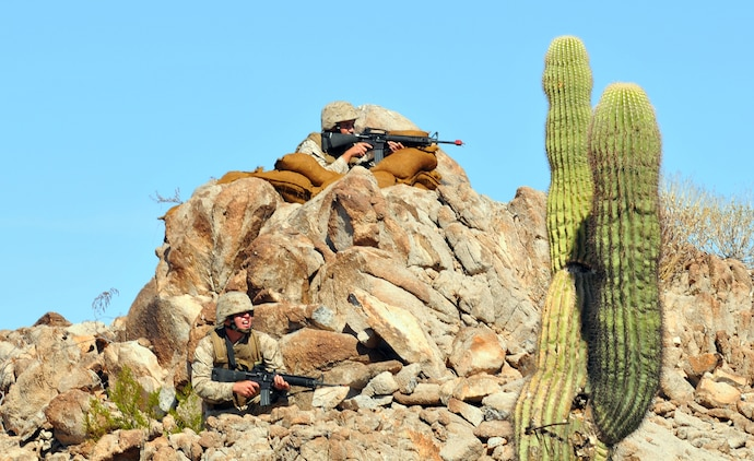 During their final exercise, two Corporal's Course students take position on a hill on the  Barry M. Goldwater Range Oct. 22, 2009. This was the first Corporal's Course held at the air station using the revised curriculum mandated throughout the Corps. The 35 students graduated Oct. 23, 2009.
