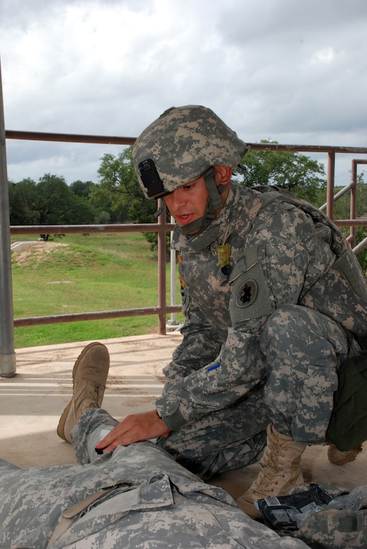 FORT SAM HOUSTON, Texas — Spc. Carlos Morales, 1st Battalion, 228th Aviation Regiment, U.S. Army South, treats a mock casualty during the U.S. Army South Soldier of the Quarter competition here. (Photo by Robert R. Ramon, U.S. Army South Public Affairs)
