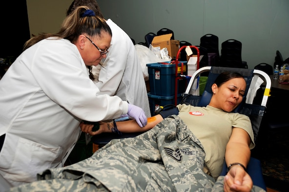 MOUNTAIN HOME AIR FORCE BASE, Idaho -- Staff Sgt. Jessica Rosario-Styles, 366th  Logistics Readiness Squadron, reacts as Dorothy Lane, Red Cross technician, inserts a needle into her arm during a blood drive Oct. 22 at the Community Center. The 366th Fighter Wing collected 121 units of blood, beating the previous record of blood donated in one day by eight units. (U.S. Air Force photo by Senior Airman Samantha Crane)