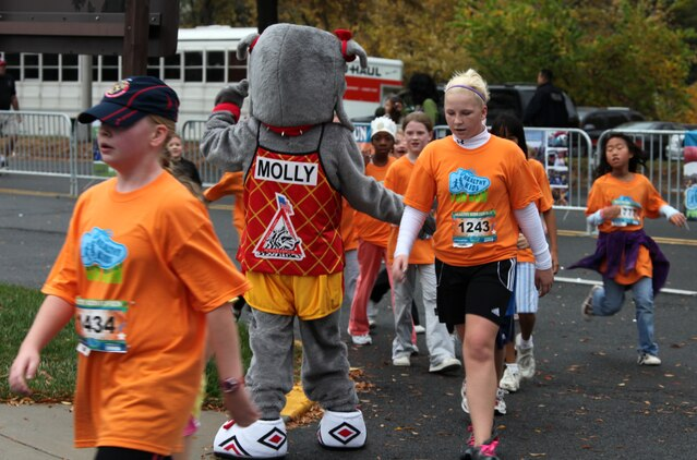 Molly, a Marine Corps Marathon mascot, congratulates runners as they cross the finish line of the Healthy Kids Fun Run in Arlington, Va., Oct. 24. About 4,000 children, ages 6 to 13, braved the cold and rain to participate in the one-mile run. The event has been a prelude to the Marine Corps Marathon for eight years.