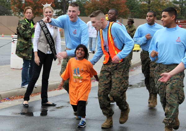 Marines who volunteered at the Healthy Kids Fun Run cheer on Sara Stachkunas, 6, as she completes the final stretch of the Healthy Kids Fun Run in Arlington, Va., Oct. 24.