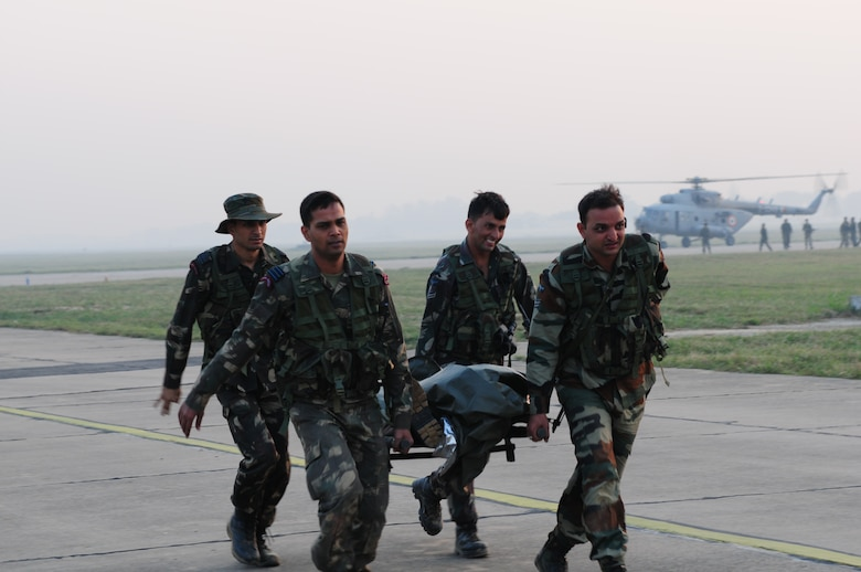 Indian Air Force medics transport a mock patient to a U.S. Air Force C-130 Hercules during a casualty evacuation exercise at Air Force Station Agra, India, Oct. 24. Cope India is a United States and India airlift exercise that provides training for humanitarian assistance and disaster relief operations. (U.S. Air Force photo/Capt. Genieve David)