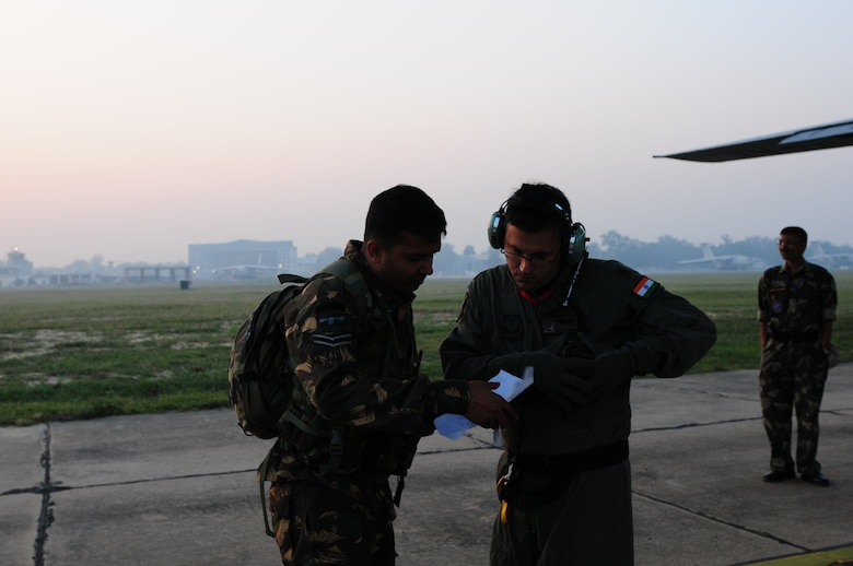 Maj. Scott Cummins, the 353rd Operations Support Squadron medical flight commander at Kadena Air Base, Japan, and a Indian Air Force medic, compare medical reports needed to transport two mock patients during a casualty evacuation exercise at Air Force Station Agra, India, Oct 24. Cope India is a United States and India airlift exercise that provides training for humanitarian assistance and disaster relief operations. (U.S. Air Force photo/Capt. Genieve David)