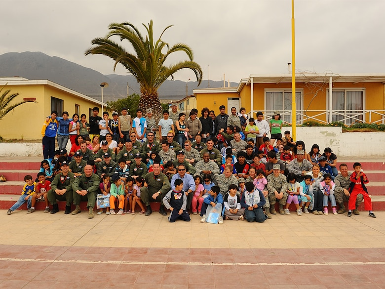 Airmen pose with children at the Aldeas SOS orphanage after visiting the home in Antofagasta, Chile for several hours on Sunday.  The Airmen were part of a more than 40 person team of US, Chilean and Argentine Air Force members who visited the home for orphaned and abandoned children while taking time off from exercise SALITRE, a five-nation event focused on coalition interoperability during peacekeeping operations. (U.S. Air Force photo by Master Sgt. Daniel Farrell)