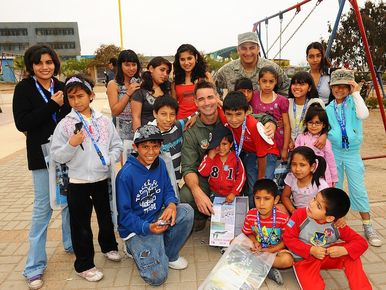 Col Roy Qualls, 159th Fighter Wing commander, and Master Sgt. David Quintero, an aircraft armament systems craftsman with the Louisiana Air National Guard pose with their new friends at the Aldeas SOS orphanage in Antofagasta, Chile.  The Airmen were part of a more than 40 person team of US, Chilean and Argentine Air Force members who visited the home for orphaned and abandoned children while taking time off from exercise SALITRE, a five-nation event focused on coalition interoperability during peacekeeping operations. (U.S. Air Force photo by Master Sgt. Daniel Farrell)