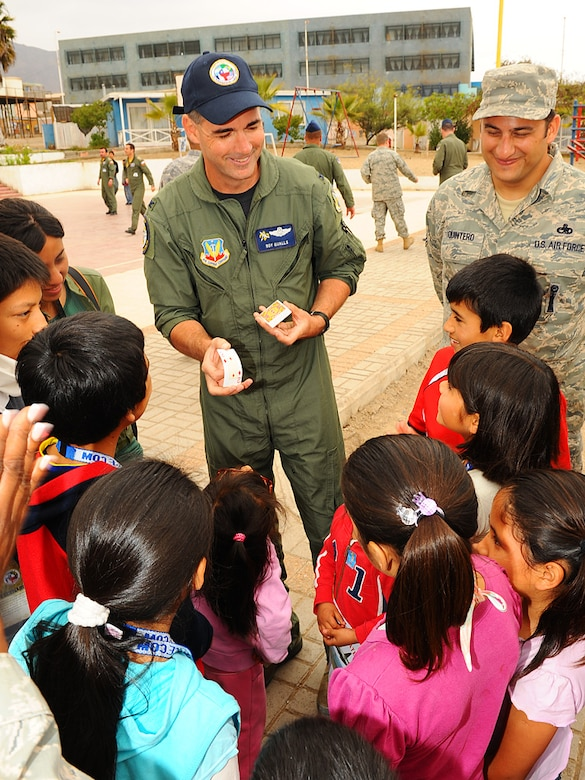 Col. Roy Qualls, 159th Fighter Wing commander, demonstrates a card trick for children at the Aldeas SOS orphanage in Antofagasta, Chile.  More than 40 Airmen from the Louisiana Air National Guard, 12th Air Force (Air Forces Southern) and the Chilean and Argentine Air Forces visited the organization for an afternoon of games and fun with the children.   (U.S. Air Force photo by Master Sgt. Daniel Farrell)