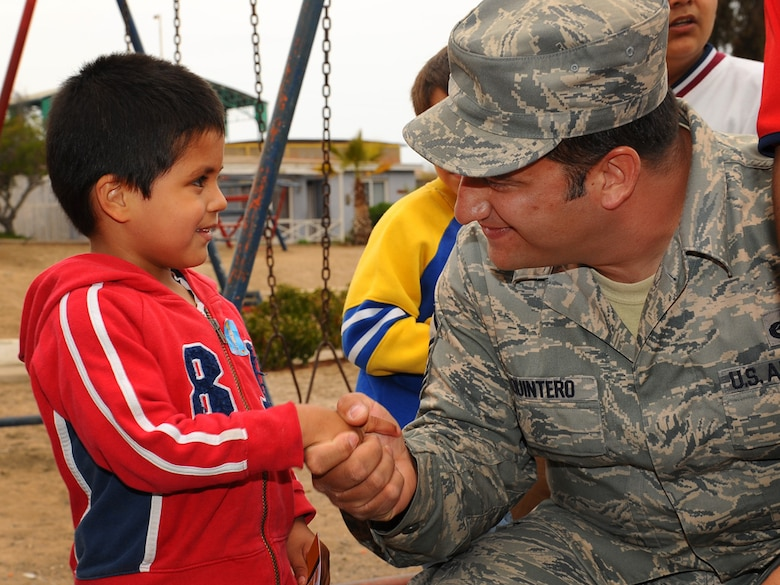 Master Sgt. David Quintero, an aircraft armament systems craftsman, with the 159th Fighter Wing, Louisiana Air National Guard, shakes the hand of child at the Aldeas SOS orphanage in Antofagasta, Chile.  Sergeant Quintero celebrated his own birthday at the center along with more than 40 Airmen from the US, Chilean and Argentine Air Forces who visited the home while taking time off from exercise SALITRE, a five-nation exercise focused on peacekeeping operations.  (U.S. Air Force photo by Master Sgt. Daniel Farrell)