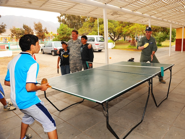 Col. Roy Qualls, the 159th Fighter Wing commander, plays ping-pong with a child at the Aldeas SOS orphanage in Antofagasta, Chile.  The Colonel and his team accompanied members of the Chilean Air Force, Argentine Air Force and 12th Air Force (Air Forces Southern) to the home for orphaned and abandoned children during exercise SALITRE.  More than 40 Airmen visited, played and distributed donated items to the 120 children who are residents at the organization´s compound.