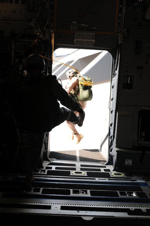Tech. Sgt. John Gaona, jumpmaster during Cope India, executes a static jump out of a C-17 Globemaster III. Cope India is a United States and India airlift exercise that provides training for humanitarian assistance and disaster relief operations. (U.S. Air Force photo/ Capt. Genieve David)
