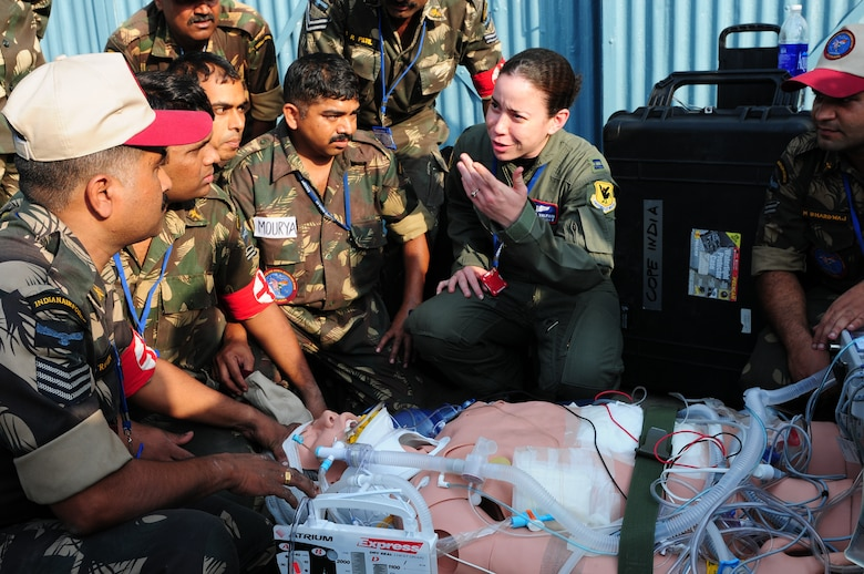 U.S. Air Force Capt. Veronica Valerio, from the 18th Wing, Kadena Air Base, Japan, explains to several Indian air force medics emergency response techniques to a mannequin patient during a U.S. Air Force combat casualty demonstration at Cope India at Air Force Station Agra, India. Cope India is a United States and India airlift exercise that provides training for humanitarian assistance and disaster relief operations. (U.S. Air Force photo/Capt. Genieve David)