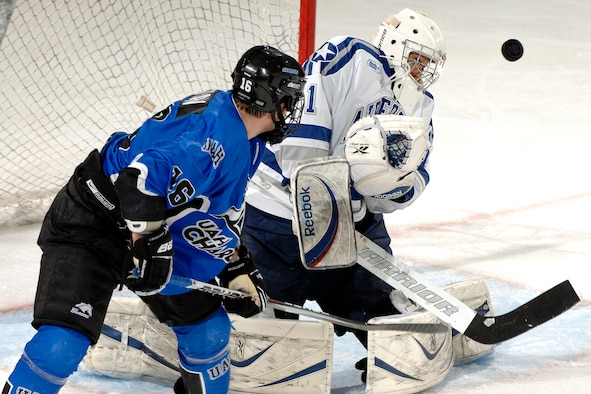 Air Force goalie Andrew Volkening, seen here (right) blocking a shot by Alabama-Huntsville forward Tom Train during the Falcons-Chargers game at the Cadet Ice Arena Oct. 17, 2009, was selected as the Atlantic Hockey Association's goalie of the week for earning two wins against the Rochester Institute of Technology Oct. 23-24. This is the 10th time Volkening, a senior and native of Genoa, Ill., has received the award. (U.S. Air Force photo/Mike Kaplan)