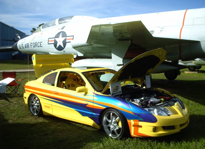 A Pontiac Sunfire with a custom paint job is parked beside an F-101 at the 2009 Commando Cruise-In at the Air Force Armament Museum Oct. 24. Some of the museum's static plane displays served as backdrops for entries in different car categories.  (U.S. Air Force photo by Airman 1st Class Joe McFadden.)