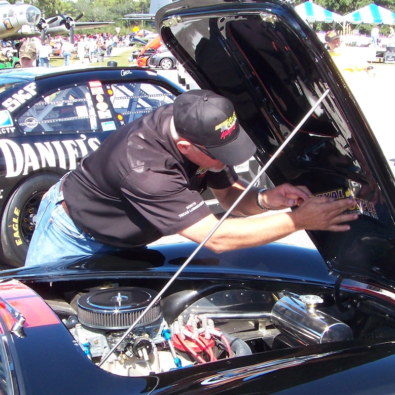 A man affixes a decal under the hood of a Ford Shelby at the 2009 Commando Cruise-In at the Air Force Armament Museum Oct. 24. Several owners had unique custom designs and logos branded on their cars for the show. (U.S. Air Force photo by Airman 1st Class Joe McFadden.)