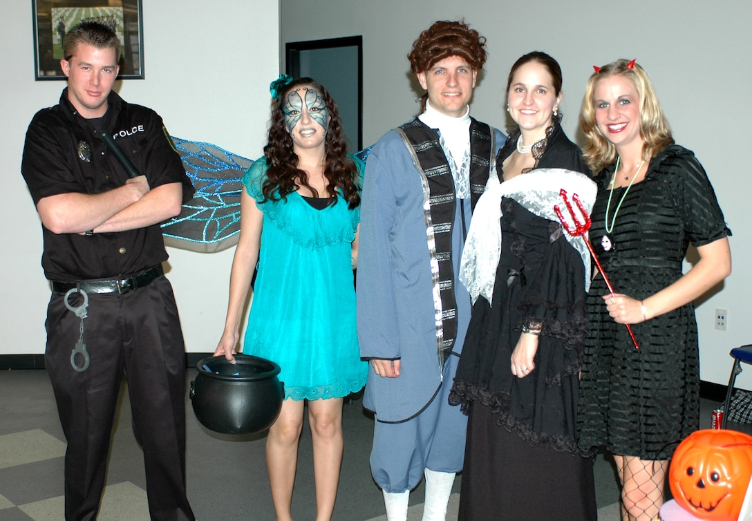 (From the left) Airman First Class Andrew Czarnowski, Staff Sgt. Robin Hinton, Brian Estes, Tech. Sgt. Heidi Estes, and Holly Thiel dress in Halloween costumes to man the Junior Enlisted Council's cake walk booth in the dining facility. (Air National Guard photo by Maj. Gabe Johnson)