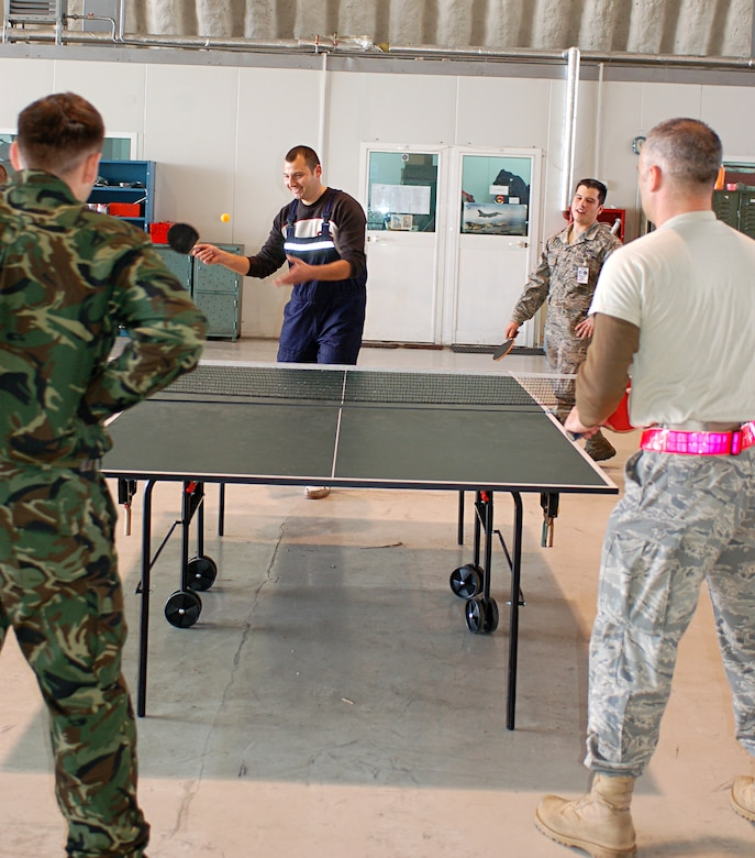 CAMPIA-TURZII, Romania -- Airmen from the 52nd Fighter Wing play pingpong with members of he Romanian air force in a shared hangar here. About 250 52nd FW Airmen and five A-10 Thunderbolt IIs are part of Dacian Thunder, a month-long combined training exercise focused on combat search and rescue, air-to-air and air-to-ground, and weapons delivery missions. During their spare time, Romanian and American Airmen challenged each other to matches on the pingpong table, which stood between the 52nd Fighter Wing's designated maintenance area and Romanian air force's MiG-21 maintenance area. (U.S. Air Force photo/2nd Lt. Kathleen Polesnak)