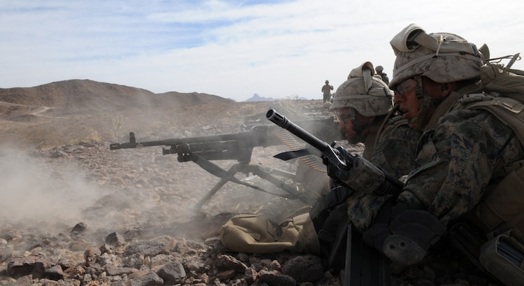 Machine gunner Pfc. Nathan McBride, left, and assistant gunner Lance Cpl. Adrian Cuevas with Company C, 1st Battalion, 2nd Marine Regiment, lay down suppressive fire with an M-240B machine gun during a company-sized exercise at the U.S. Army Yuma Proving Ground in Arizona, Oct. 27, 2009. The Camp Lejeune, N.C.-based battalion spent approximately one month the Yuma area, making use of its surroundings' rocky, mountainous terrain in preparation for a deployment to Afghanistan early next year. The exercise stressed the approximately 220-Marine force to use combined arms tactics, ranging from rifles and machine guns to mortars and TOW missiles. Cuevas, 24, is a Los Angeles-native and McBride, 20, is a Cincinnati-native.