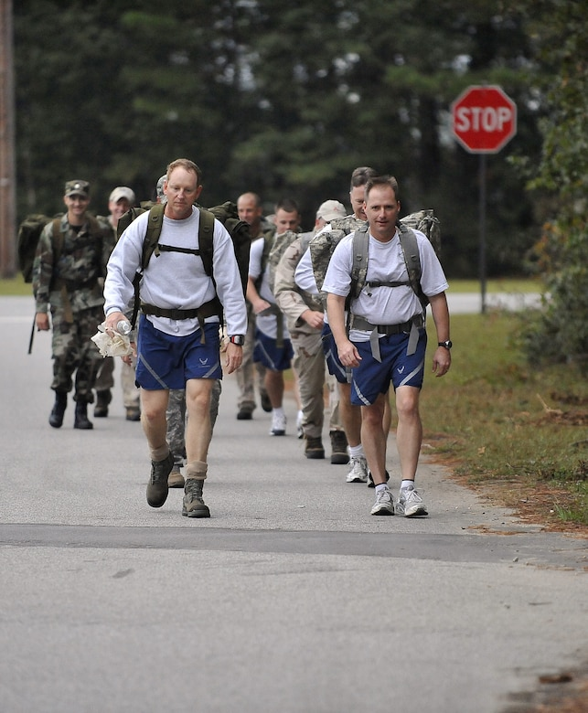 Col. John Wood, right, and Col. Benjamin Wham and lead 437th Civil Engineer Squadron Explosive Ordnance Disposal Flight members on a ruck march here Oct. 27. The EOD personnel train with ruck sacks to prepare for embedding with sister services and foreign special forces in a dismounted capacity while deployed. Colonel Wood is the 437th Airlift Wing commander and Colonel Wham is the 437th Mission Support Group commander. (U.S. Air Force photo/James Bowman)