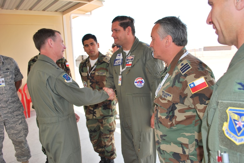 ANTOFAGASTA, Chile -- Lt Gen Glenn Spears, 12th Air Force (Air Forces Southern) commander, hands a commander´s coin to Chilean Air Force Lt. Col. Herman Olave, an Air Operations Center specialist participating in exercise SALITRE.  The commander visited the exercise site here with a delegation of senior staff representing the five participating nations--Chile, Argentina, France, Brazil and the United States--and had the opportunity to recognize outstanding performers working in the exercise during his visit.  (Courtesy photo)