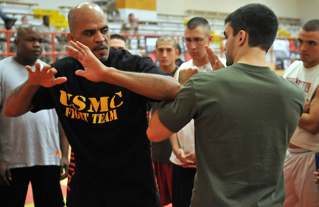 """Jorge """"El Conquistador"""" Rivera, mixed martial arts fighter, and Matt Phinney, boxing instructor, demonstrate striking techniques for Marines in the gym at the Marine Corps Air Station in Yuma, Ariz., Oct. 28, 2009. Train the Troops, sponsored and organized by Ranger Up, an MMA clothing company, visited the station to teach Marines mixed martial arts."""