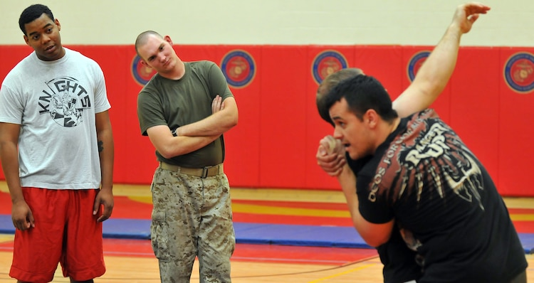 Station Marines look on as Nick Palmisciano, Ranger Up president, puts Army National Guard Staff Sgt. Tom Amenta in a choke hold during the Train the Troops seminar in the gym at the Marine Corps Air Station in Yuma, Ariz., Oct. 28, 2009. Train the Troops, sponsored and organized by Ranger Up, a mixed martial arts clothing company, visited the station to teach Marines MMA techniques.