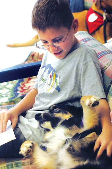 Dylan Fiveash reads to Nora, the therapy dog. U. S. Air Force photo by Sue Sapp