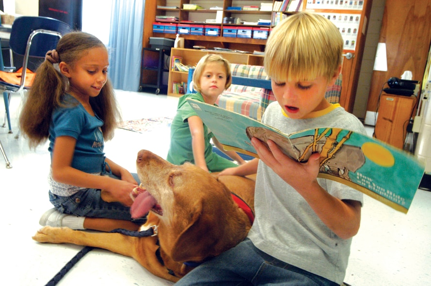 Second grade student, Kade Daniels reads as Shelby Imel and Lindsey Autry listen and interact with Buddy. Buddy is a certified therapy dog who visits schools, hospitals and nursing homes. U. S. Air Force photo by Sue Sapp
